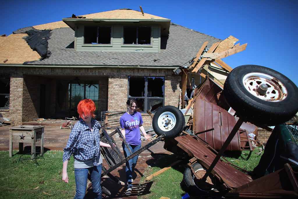 . EL RENO, OK - JUNE 01:  Michelle Demers (L) and Amanda Demers carry a rocking chair from the  damaged home of a family friend after a tornado hit on June 1, 2013 in El Reno, Oklahoma. The tornado ripped through the area last night killing at least nine people, injuring many others and destroying homes and buildings.  (Photo by Joe Raedle/Getty Images)