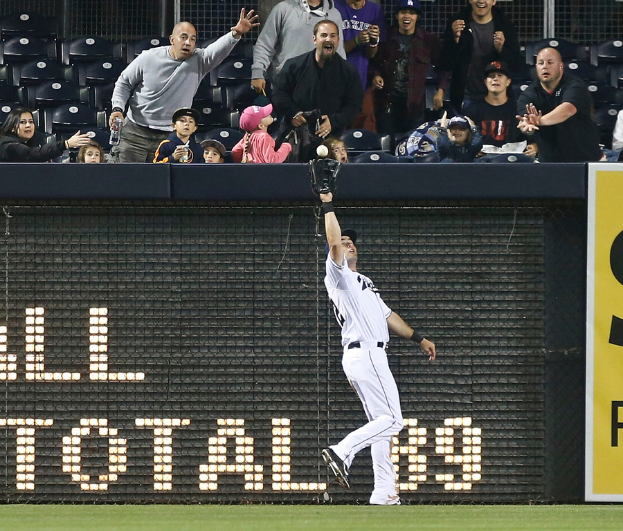 . San Diego Padres left fielder Seth Smith reaches back to make the running catch at the wall on a drive hit by Colorado Rockies\' Justin Morneau in the fifth inning of a baseball game Monday, April 14, 2014, in San Diego. (AP Photo/Lenny Ignelzi)