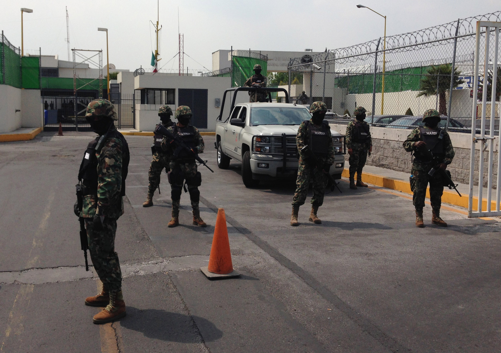 """. Mexican Navy Marines guard the entrance to a navy hangar where Mexican drug lord Joaquin \""""El Chapo\"""" Guzman is expected to arrive in Mexico City, Saturday, Feb. 22, 2014. A senior U.S. law enforcement official said Saturday, that Guzman, the head of Mexico�s Sinaloa Cartel, was captured alive overnight in the beach resort town of Mazatlan. Guzman faces multiple federal drug trafficking indictments in the U.S. and is on the Drug Enforcement Administration�s most-wanted list.  (AP Photo/Dario Lopez-Mills)"""