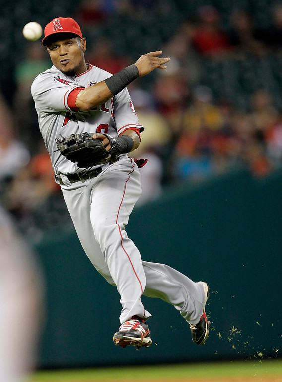 . HOUSTON, TX - SEPTEMBER 14:  Erick Aybar #2 of the Los Angeles Angels of Anaheim throws to first base but can\'t retire Jimmy Paredes #38 of the Houston Astros at Minute Maid Park on September 14, 2013 in Houston, Texas.  (Photo by Bob Levey/Getty Images)