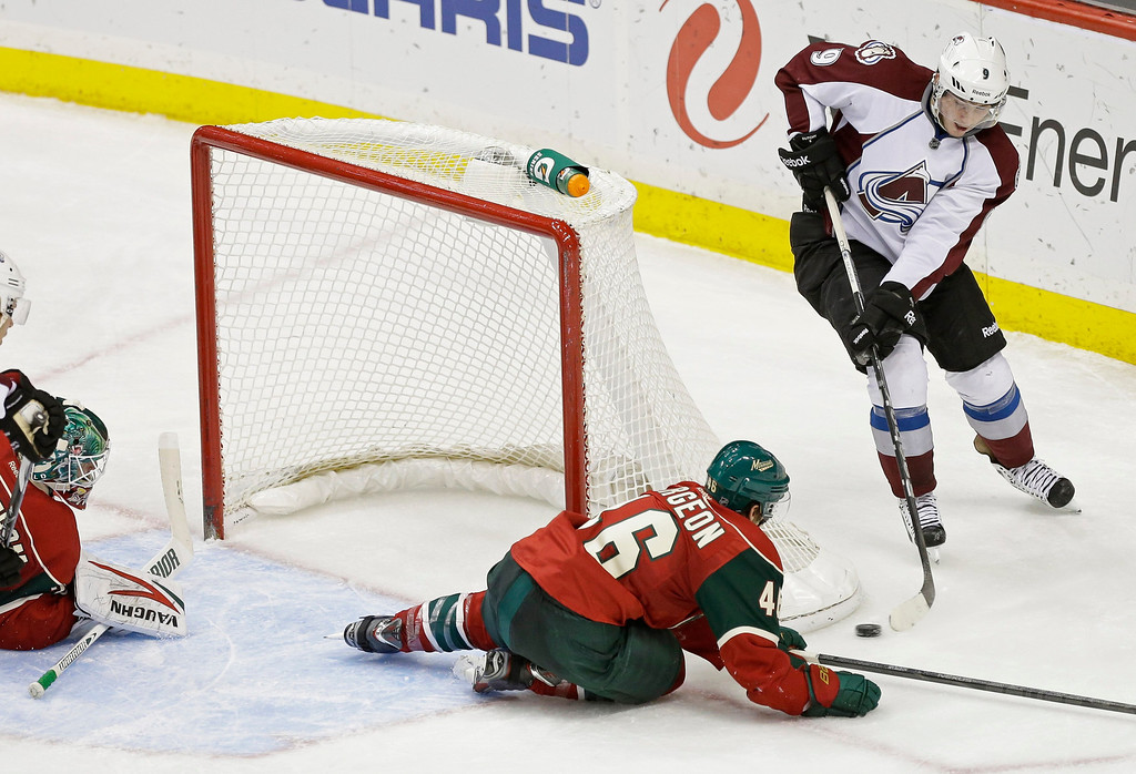 . Minnesota Wild goale Niklas Backstrom, left, of Finland, looks on as Colorado Avalanche\'s Matt Duchene, right, scores a game-tying goal that deflected into the net off  Wild\'s Jared Spurgeon in the third period of an NHL hockey game on Thursday, Feb. 14, 2013, in St. Paul, Minn. The Avalanche won 4-3 in a shootout, with Duchene providing the winning goal. (AP Photo/Jim Mone)