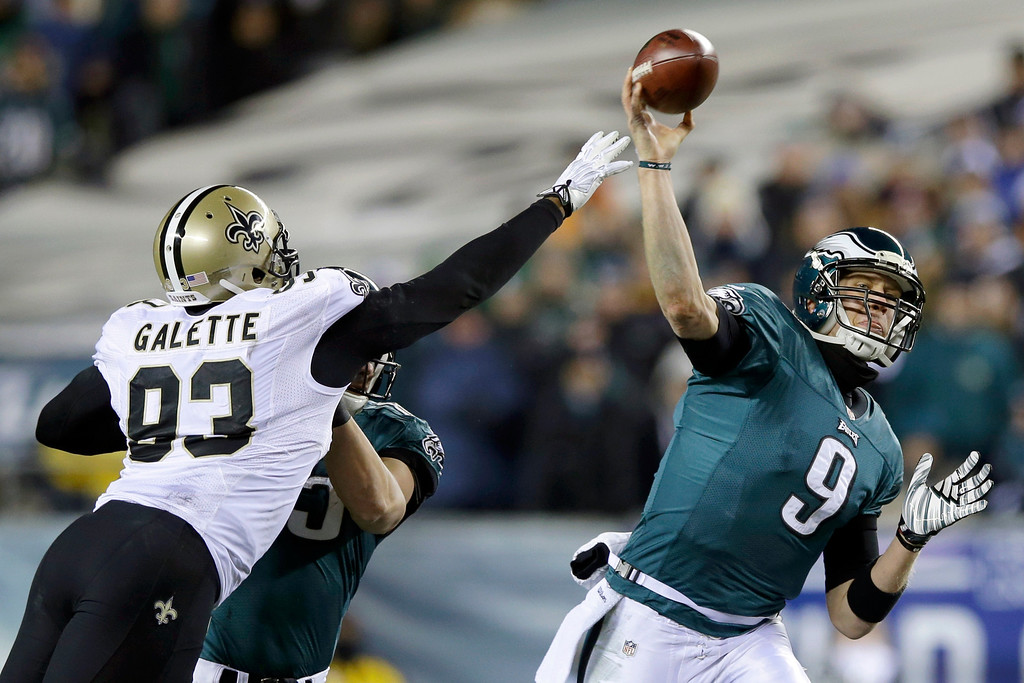 . Philadelphia Eagles\' Nick Foles (9) passes as New Orleans Saints\' Junior Galette (93) tries to block during the first half of an NFL wild-card playoff football game, Saturday, Jan. 4, 2014, in Philadelphia. (AP Photo/Michael Perez)