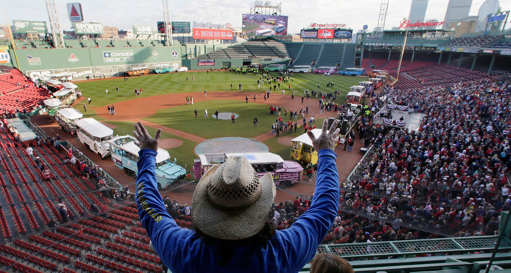 . Carlos Arredondo raises his arms as he waves to fans at Fenway Park in advance of the Boston Red Sox\'s championship parade in celebration of the baseball team\'s World Series win, Saturday, Nov. 2, 2013, in Boston. (AP Photo/Charles Krupa)