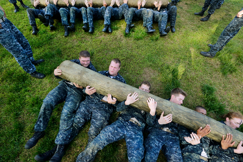 """. Freshman midshipmen, known as \""""plebes,\"""" perform sit ups with a log across their chests during Sea Trials, a day of physical and mental challenges that caps off their first year at the U.S. Naval Academy in Annapolis, Md., Tuesday, May 13, 2014. (AP Photo/Patrick Semansky)"""
