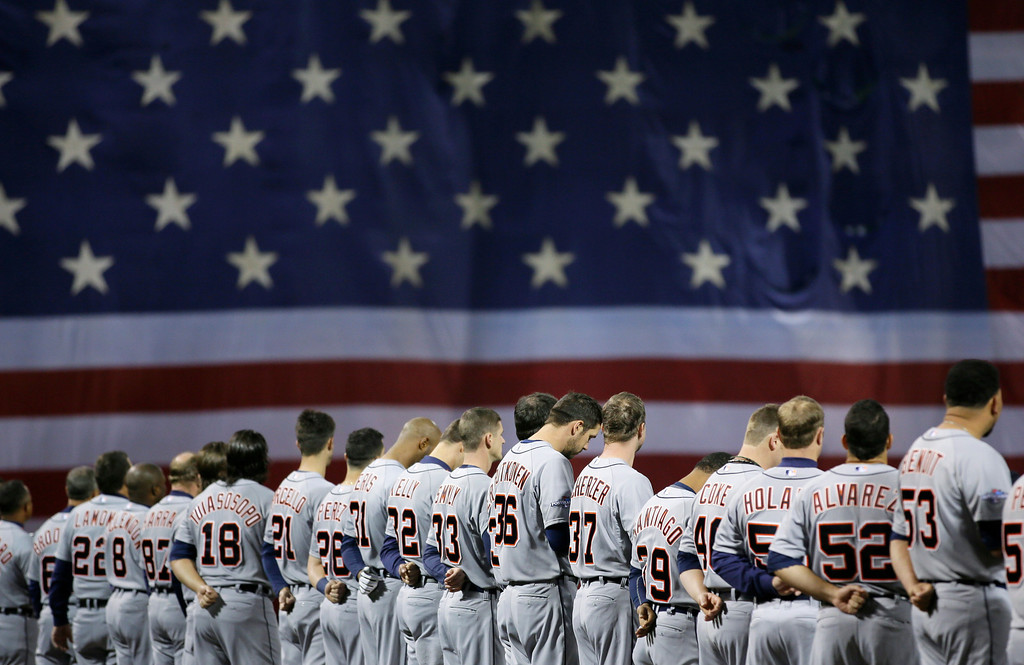. Detroit Tigers players stand in front of a giant American flag during the national anthem before Game 1 of the American League baseball championship series against the Boston Red Sox Saturday, Oct. 12, 2013, in Boston. (AP Photo/Matt Slocum)
