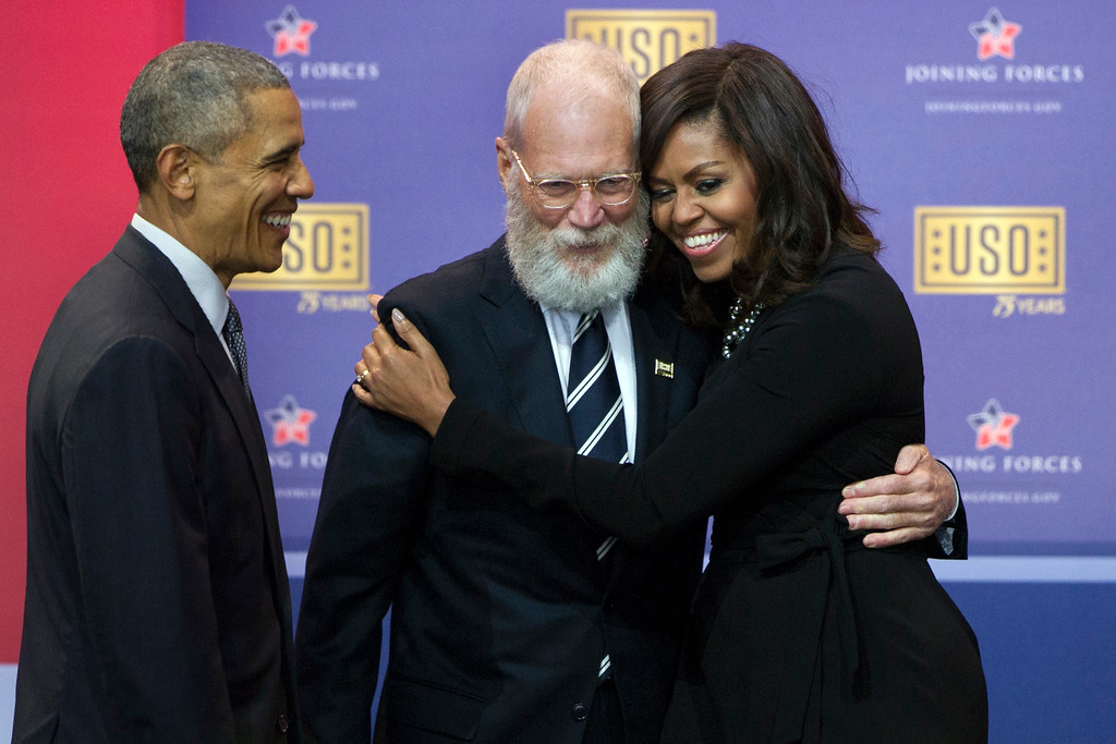 . President Barack Obama looks on as first lady Michelle Obama and comedian David Letterman hug during a comedy show presented by the United Service Organizations (USO) and the military at  Andrews Air Force Base, Thursday, May 5, 2016. The event marks the USO\'s 75th anniversary and the 5th anniversary of Joining Forces.  (AP Photo/Cliff Owen)