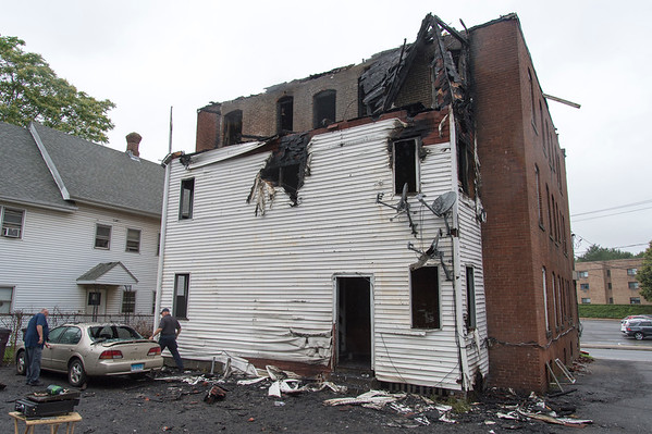 06/25/19 Wesley Bunnell | Staff A fire broke out at a three floor residence at 39 South Whiting St in New Britain on Monday June 24, 2019 at approximately 8pm with firefighters on the scene until approximately 4am Tuesday morning. Fire investigators , L, work on shutting off the alarm on a damaged car parked in the rear. Damage to the third floor is visible above the covered staircase.