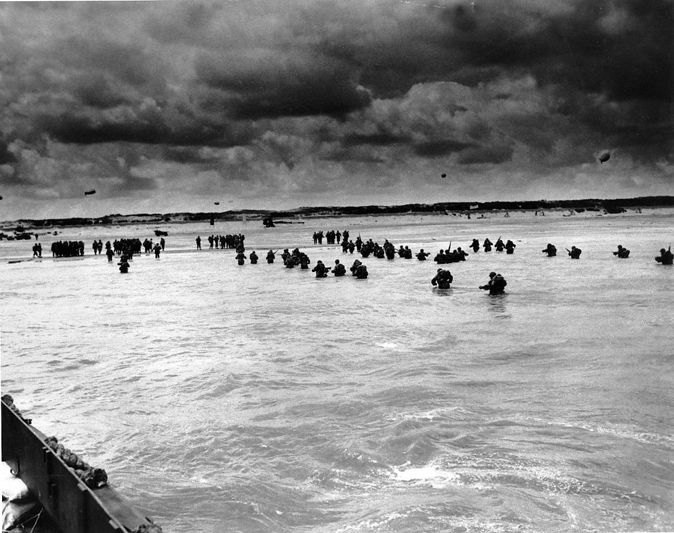 . U.S. reinforcements wade through the surf as they land at Normandy in the days following the Allies\' June 1944, D-Day invasion of occupied France.  (AP Photo/Peter Carroll)
