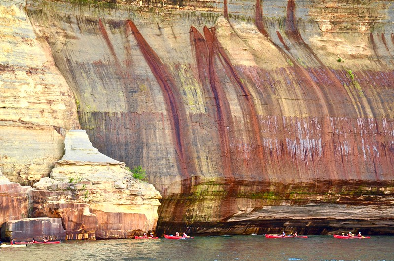 kayakers in the water at the bottom of a cliff