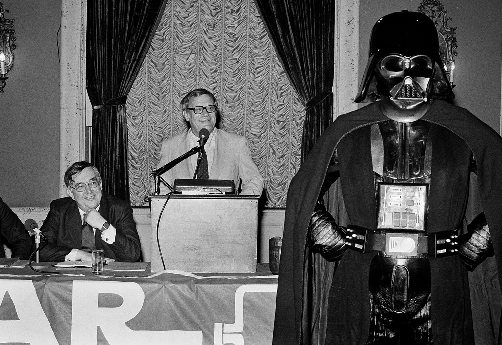 . Aubrey Singer, left, managing director of British Broadcasting Corp. Radio and Frank Mankiewicz, center, president of National Public Radio, announce at a news conference in Los Angeles, Calif., that NPR will produce with the BBC a radio series based on Star Wars, April 27, 1979. At right is Darth Vader, the villain of the Star Wars films, who made a surprise appearance. (AP Photo/Wally Fong)