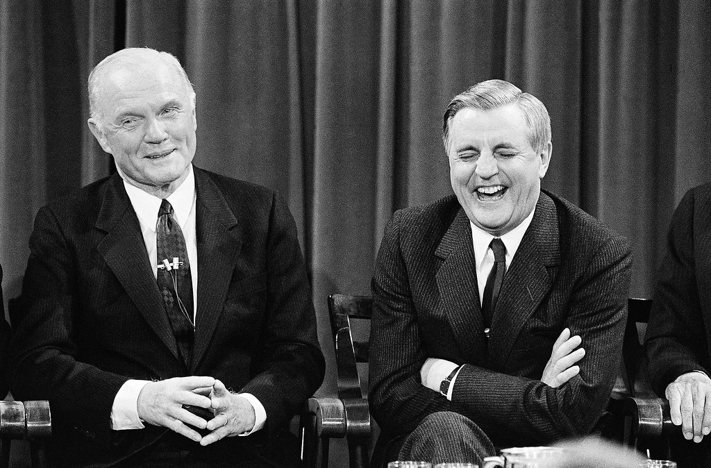 . Walter Mondale, right, reacts as Sen. John Glenn tries to get some rebuttal time, during a forum for presidential candidates at the John F. Kennedy School of Government at Harvard University, Jan. 31, 1984, Cambridge, Mass. The Democrats staged a gentlemanly debate on foreign policy issues. (AP Photo/David Tenenbaum)