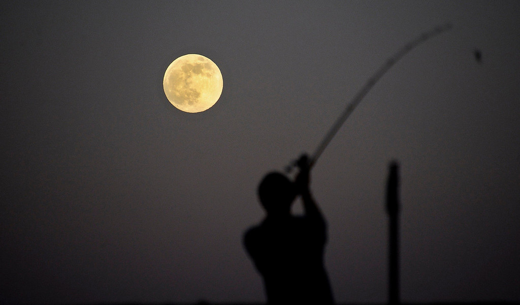 ". Local residents do some fishing as the largest full moon of 2013, also referred to as a ""super moon,\"" rises in Little Rock, California on June 22, 2013.  REUTERS/Gene Blevins"