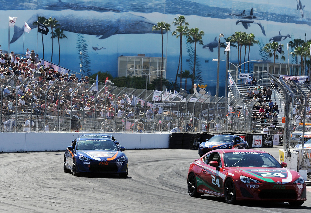 . (Will Lester/Staff Photographer)  Adam Carolla (right) leads Mark Steines (left) and Michael Trucco (left rear) as Dave Pasant (rear right) enters turn 10 during the Pro and Celebrity qualifying session April 19, 2013 at the 39th annual Toyota Grand Prix of Long Beach.