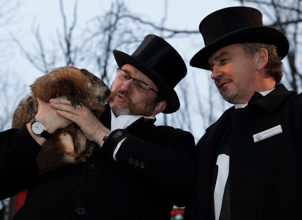 . Ben Hughes, left, and John Griffiths, handlers of the weather-predicting groundhog Punxsutawney Phil, holds Phil after removing him from his stump at Gobbler\'s Knob on Groundhog Day, Monday, Feb. 2, 2009, in Punxsutawney, Pa. The Groundhog Club said Phil saw his shadow and predicted six more weeks of winter. (AP Photo/Carolyn Kaster)
