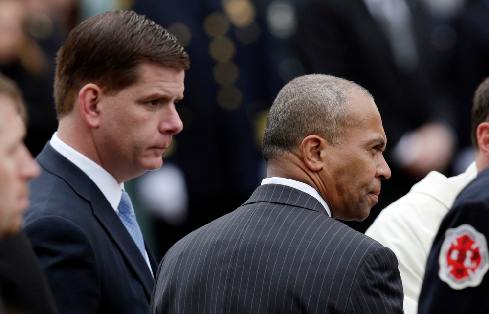 Description of . Boston Mayor Martin Walsh, left, and Mass. Gov. Deval Patrick watch as the casket of Boston Fire Lt. Edward Walsh is carried on Engine 33  as it departs St. Patrick's Church in Watertown, Mass., Wednesday, April 2, 2014. Walsh and his colleague Michael Kennedy died after being trapped while battling a nine-alarm apartment fire in Boston on March 26. (AP Photo/Charles Krupa)