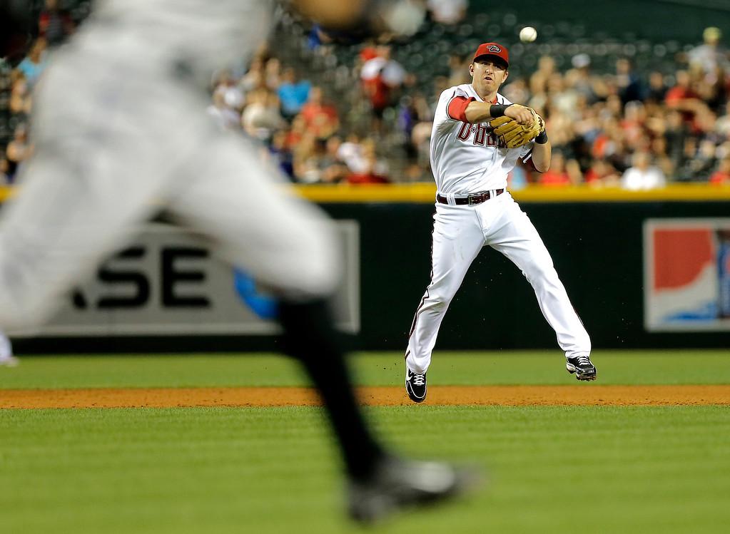 . Arizona Diamondbacks\' Cliff Pennington throws out Colorado Rockies\' Dexter Fowler during the ninth inning of a baseball game, Friday, April 26, 2013, in Phoenix. (AP Photo/Matt York)
