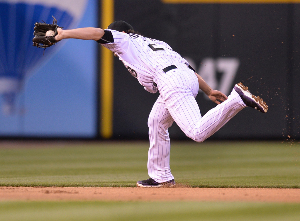 . DENVER, CO - APRIL 5:  Colorado shortstop Charlie Culberson made backhand grab of the ball of the bat of Arizona\'s Chris Owings in the second inning. Owings made it to first base safely. The Colorado Rockies hosted the Arizona Diamondbacks Saturday night, April 5, 2014 in Denver. (Photo by Karl Gehring/The Denver Post)