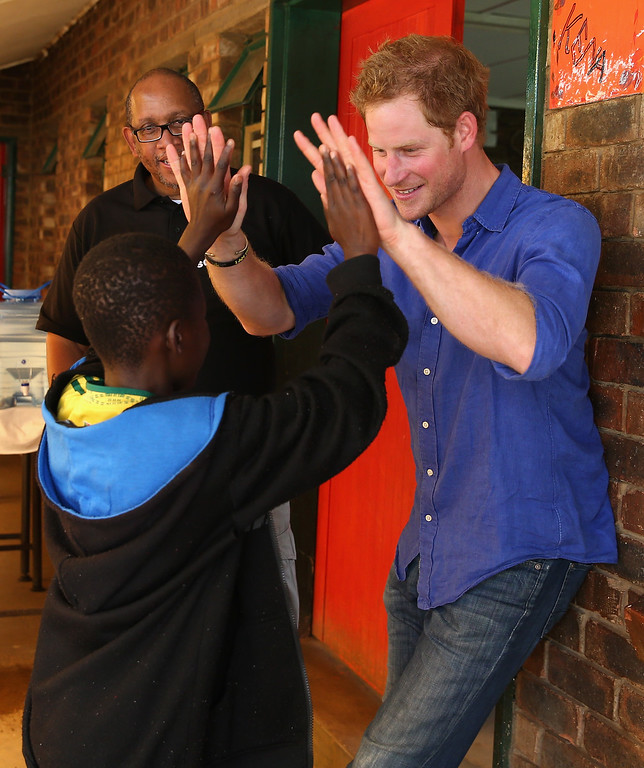 . Prince Harry and Prince Seeiso of Lesotho talk to a child living with HIV during a visit to a Mamohato Network Club for children living with HIV at St Paul Centre on December 9, 2014 in Maseru, Lesotho.  (Photo by Chris Jackson/Getty Images for Sentebale)