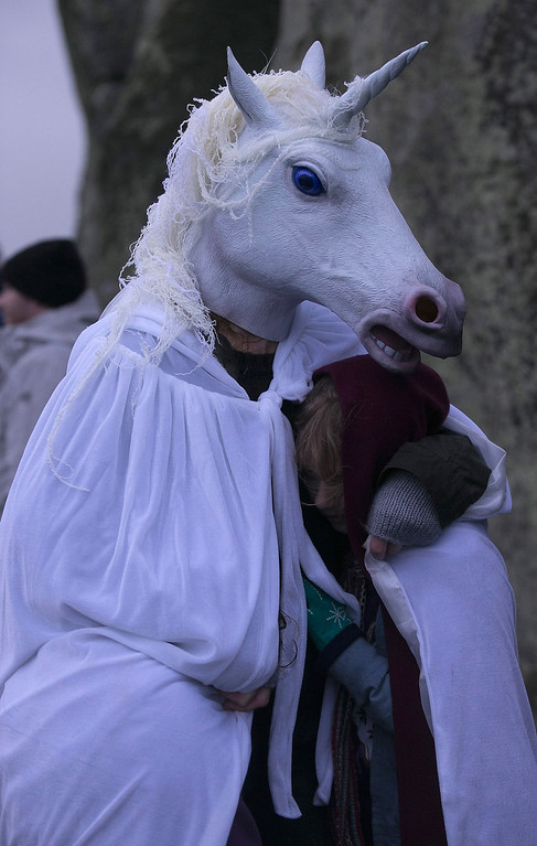 . A woman wearing a unicorn mask shelters a girl as druids, pagans and revelers gather, hoping to see the sun rise as they take part in a winter solstice ceremony at Stonehenge on December 21, 2013 in Wiltshire, England.  (Photo by Matt Cardy/Getty Images)