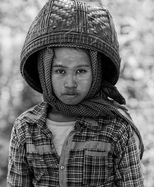Portrait of a countryside laborer wearing a basket over her head as protection from the sun.  Myanmar 2017