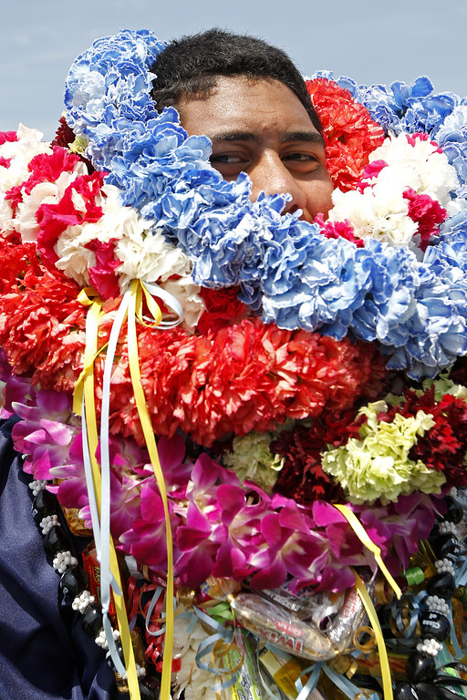 . Senior Leroy Tanoai is covered with leis from family and friends after the graduation ceremony on the high school football field on Saturday, June 01, 2013 in Sherman Oaks, CA.  Photo by Michael Yanow
