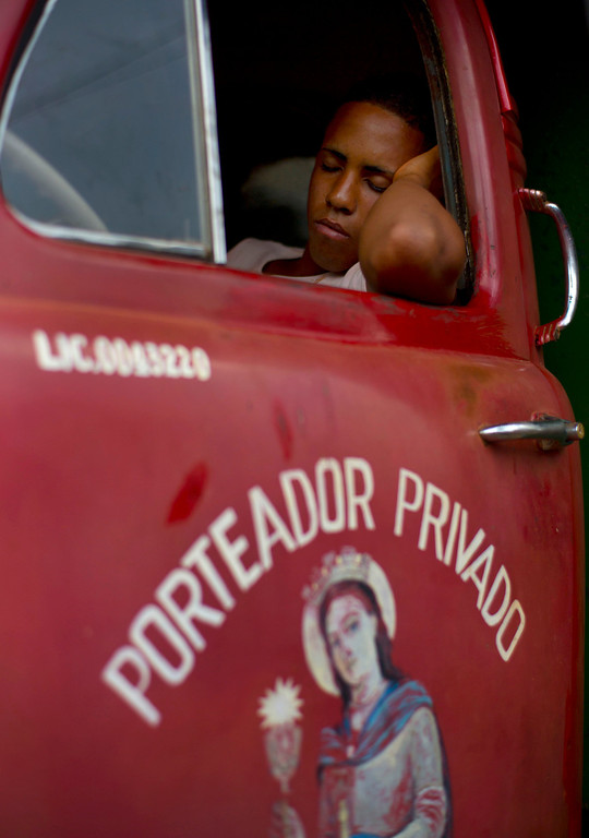 . In this Sept. 30, 2013 photo, a private driver rests in his truck loaded with fruits and vegetables before the 114th Street Market opens on the outskirts of Havana, Cuba. Produce is brought in by growers themselves and by transportation specialists who make a living by buying crops far away and hauling them to Havana, the islandís biggest and most important market. (AP Photo/Ramon Espinosa)