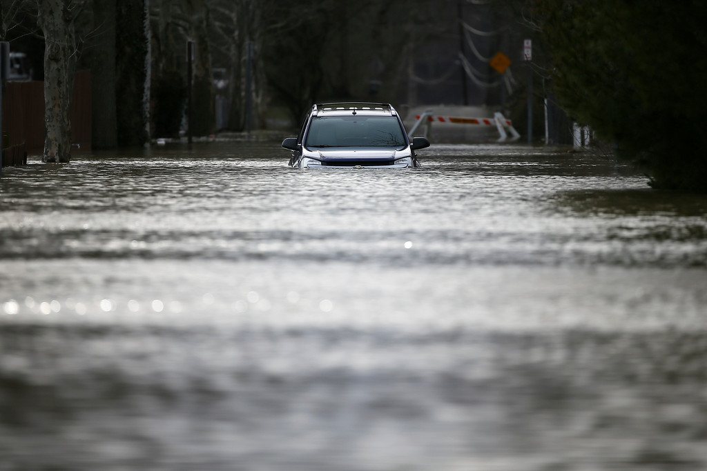 . A vehicle is submerged along Waits Avenue in Cincinnati, Sunday, Feb. 25, 2018, in Cincinnati. Heavy rains overnight have sent the swollen Ohio River to its highest point in 20 years with the river expected to remain above flood stage through the end of the week, a National Weather Service meteorologist said Sunday. (Kareem Elgazzar/The Cincinnati Enquirer via AP)