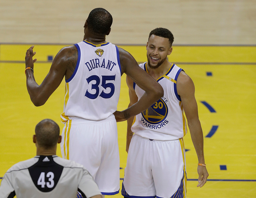 . Golden State Warriors forward Kevin Durant (35) and guard Stephen Curry (30) react next to referee Dan Crawford (43) during the first half of Game 1 of basketball\'s NBA Finals between the Warriors and the Cleveland Cavaliers in Oakland, Calif., Thursday, June 1, 2017. (AP Photo/Ben Margot)