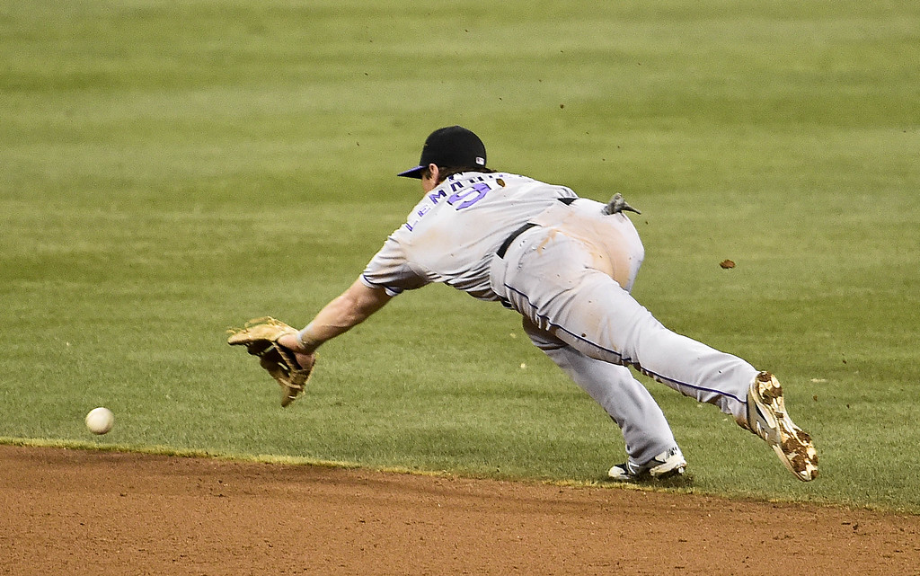 . SAN DIEGO, CA - SEPTEMBER 23:  DJ LeMahieu #9 of the Colorado Rockies dives but can\'t make the catch on a single hit by Alexi Amarista #5 of the San Diego Padres during the fifth inning of a baseball game at Petco Park September, 23, 2014 in San Diego, California.  (Photo by Denis Poroy/Getty Images)
