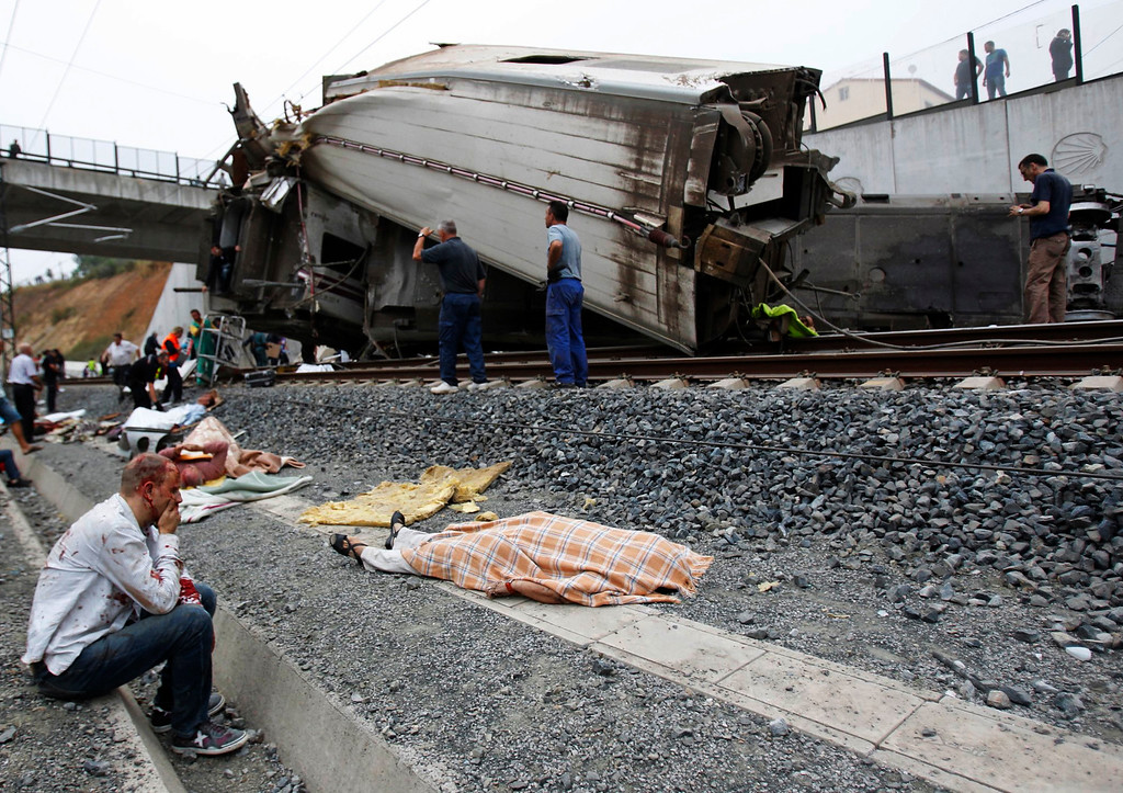 . A picture taken on July 24, 2013 shows an injured man sitting next to the body of a victim covered with a blanket following a train accident near the city of Santiago de Compostela.  AFP PHOTO / LA VOZ DE GALICIA / XOAN A. SOLER / MONICA FERREIROSMONICA FERREIROS,XOAN A. SOLER/AFP/Getty Images