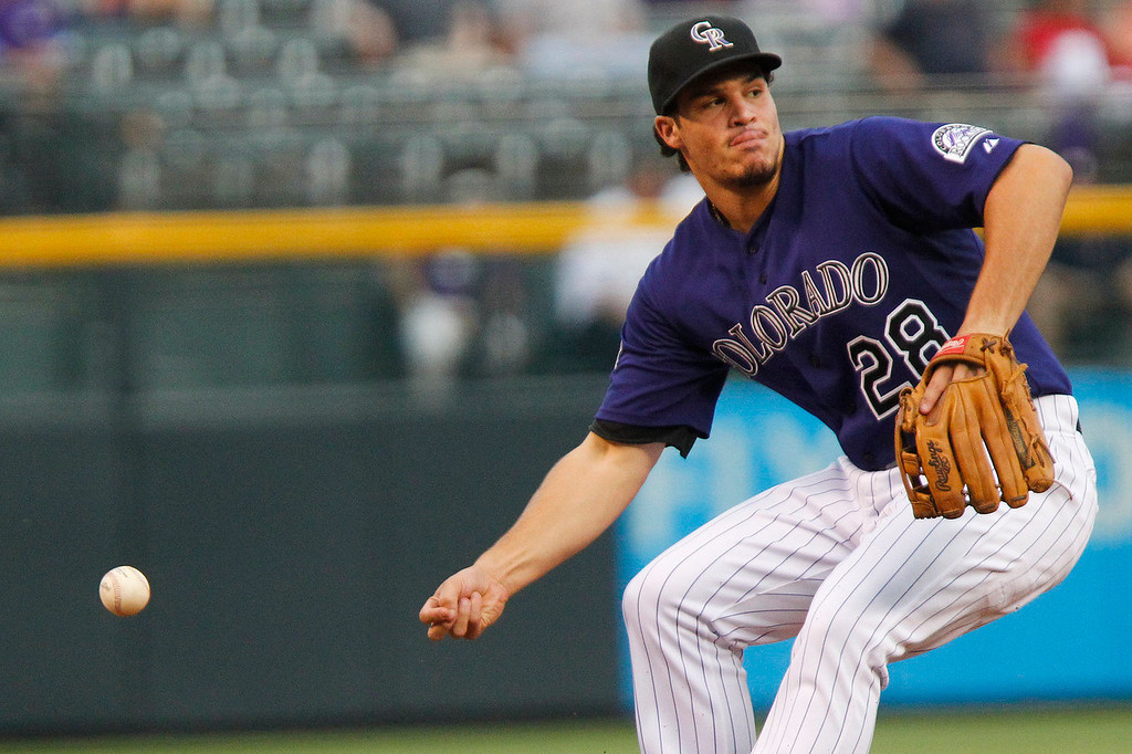 . Colorado Rockies\' Nolan Arenado misses as he tries to bare-hand a grounder by San Francisco Giants\' Marco Scutaro (19)during the first inning of a baseball game, Monday, Aug. 26, 2013, in Denver.(AP Photo/Barry Gutierrez)