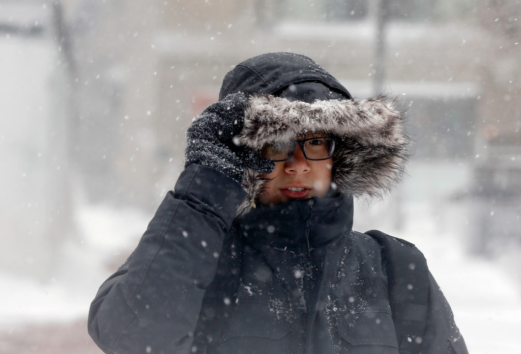 . A woman walks though falling snowflakes during a snowstorm, Tuesday, March 13, 2018, in downtown Boston. (AP Photo/Michael Dwyer)