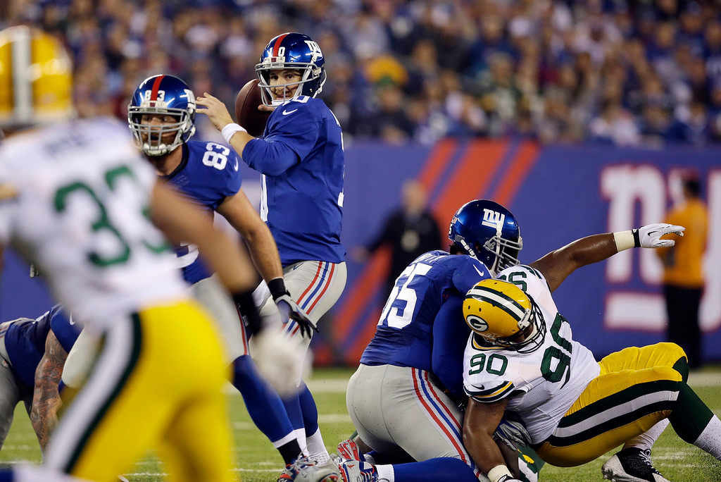 . New York Giants quarterback Eli Manning, center, throws a pass to Rueben Randle for a touchdown during the first half of an NFL football game against the Green Bay Packers, Sunday, Nov. 17, 2013, in East Rutherford, N.J. (AP Photo/Seth Wenig)