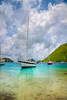 Beautiful tropical cove filled with anchored luxurious sailboats.