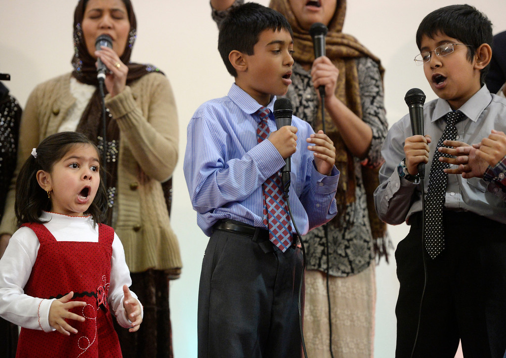 . AURORA, CO. - JANUARY 11: Sitaish Khan, below left, 4-years-old, sings along with the Indian-Pakistan Bethel Pentecostal Worship team singers during the Addis Kidan Evangelical Church dedication service, Saturday morning, January 10, 2014. (Photo By Andy Cross / The Denver Post)