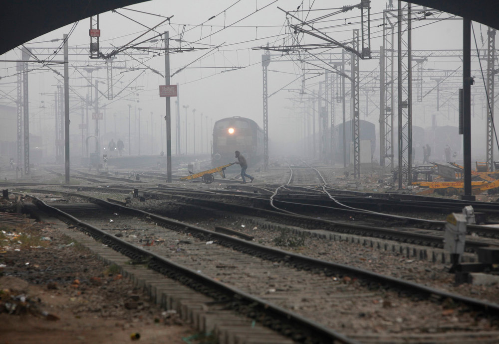 . A labourer pushes a handcart past a train as he crosses railway tracks on a foggy and cold winter morning in New Delhi January 7, 2013. REUTERS/Mansi Thapliyal