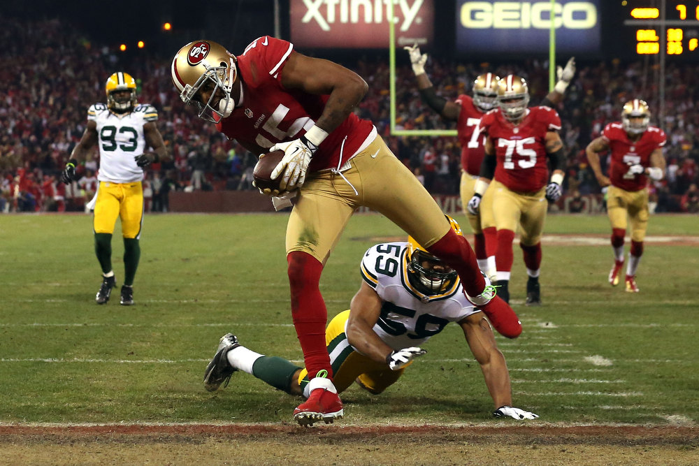 Description of . Wide receiver Michael Crabtree #15 of the San Francisco 49ers runs the ball in for a touchdown thrown by quarterback Colin Kaepernick #7 in the second quarter against the Green Bay Packers during the NFC Divisional Playoff Game at Candlestick Park on January 12, 2013 in San Francisco, California.  (Photo by Stephen Dunn/Getty Images)