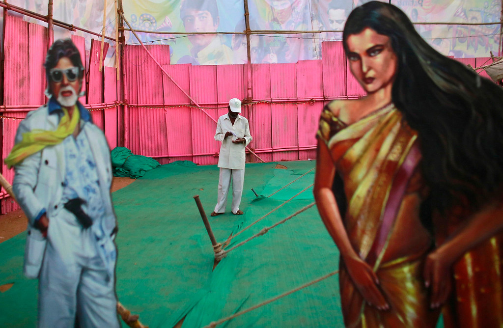 """. An employee of Anoop Touring Talkies, a travelling tent cinema company, stands between cut-outs of Bollywood actors Amitabh Bachchan and Rekha in Mumbai April 23, 2013. Indian cinema marks 100 years since Dhundiraj Govind Phalke\'s black-and-white silent film \""""Raja Harishchandra\"""" (King Harishchandra) held audiences spellbound at its first public screening on May 3, 1913, in Mumbai. Indian cinema, with its subset of Bollywood for Hindi-language films, is now a billion-dollar industry that makes more than a thousand films a year in several languages. It is worth 112.4 billion rupees (over $2 billion) and leads the world in terms of films produced and tickets sold. Picture taken April 23, 2013. REUTERS/Danish Siddiqui"""