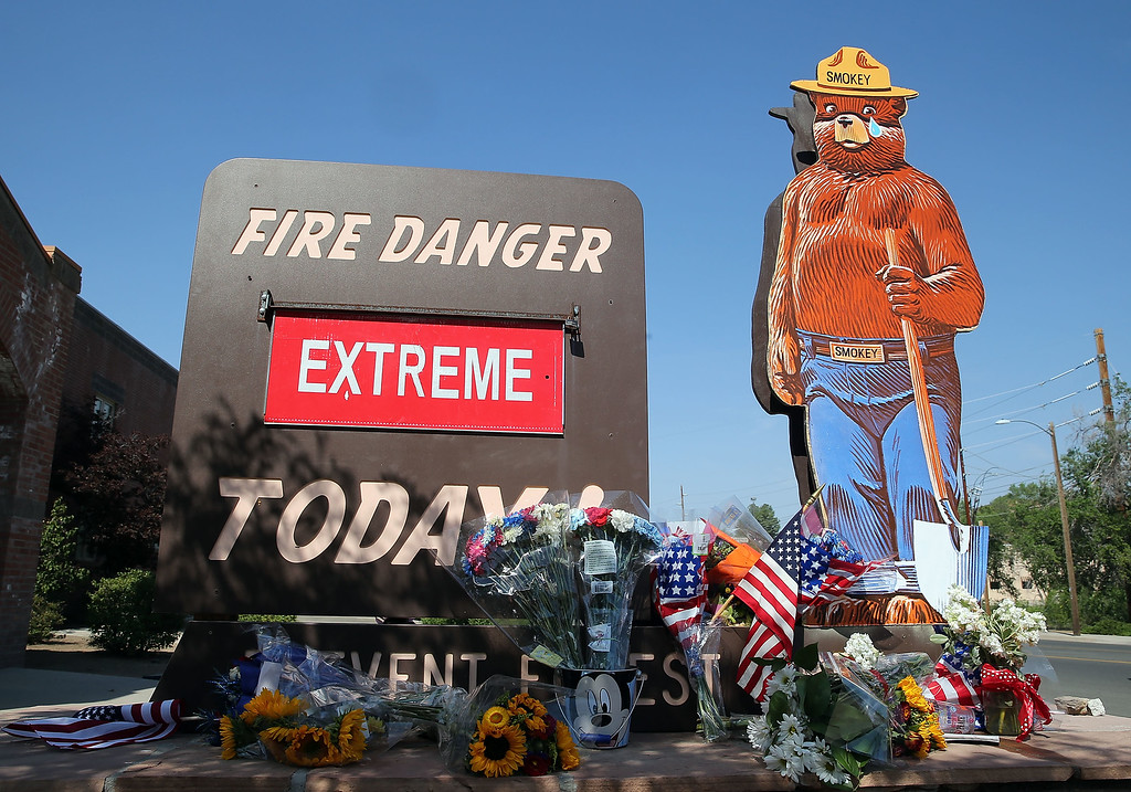 """. American flags and flowers adorn a \""""Extreme\"""" fire danger warning outside of Fire station 1 on July 2, 2013 in Prescott, Arizona.  (Photo by Christian Petersen/Getty Images)"""