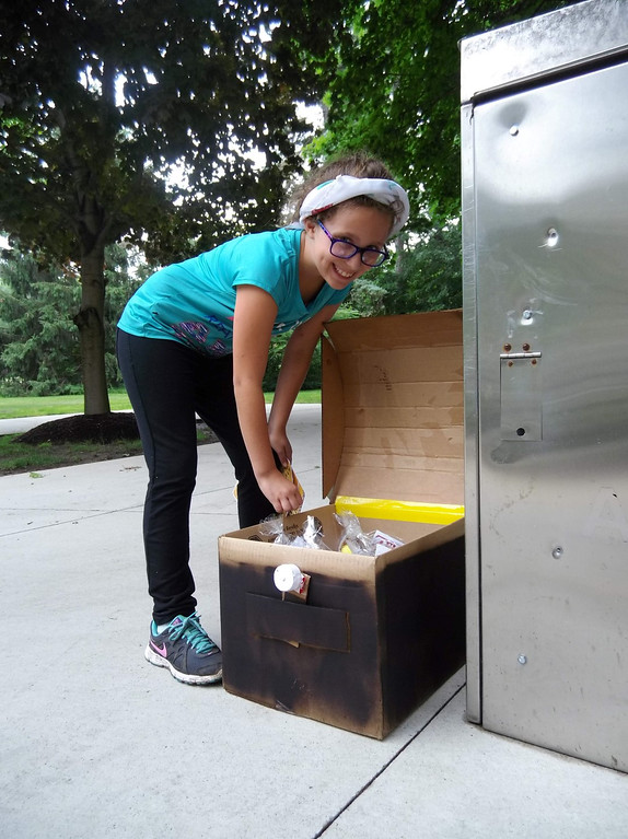 . Kara Cogan smiles as she finds the treasure chest with ocarinas hidden inside. Kara and the other kids needed to decode a puzzle to find the chest during a program at Mentor Public Library. (Courtesy Mentor Public Library)