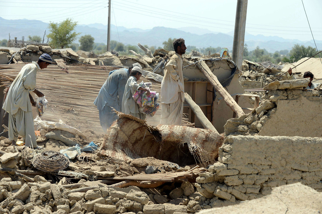 . Pakistani earthquake survivors collect their belongings in rubble of their collapsed mud houses in the earthquake-devastated district of Awaran on September 25, 2013.     AFP PHOTO/Banaras KHAN/AFP/Getty Images