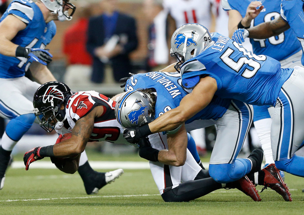 Description of . Atlanta Falcons defensive back Dominique Franks (29) is stopped by Detroit Lions free safety John Wendling (29) and linebacker Travis Lewis (50) during the first quarter of an NFL football game at Ford Field in Detroit, Saturday, Dec. 22, 2012. (AP Photo/Rick Osentoski)