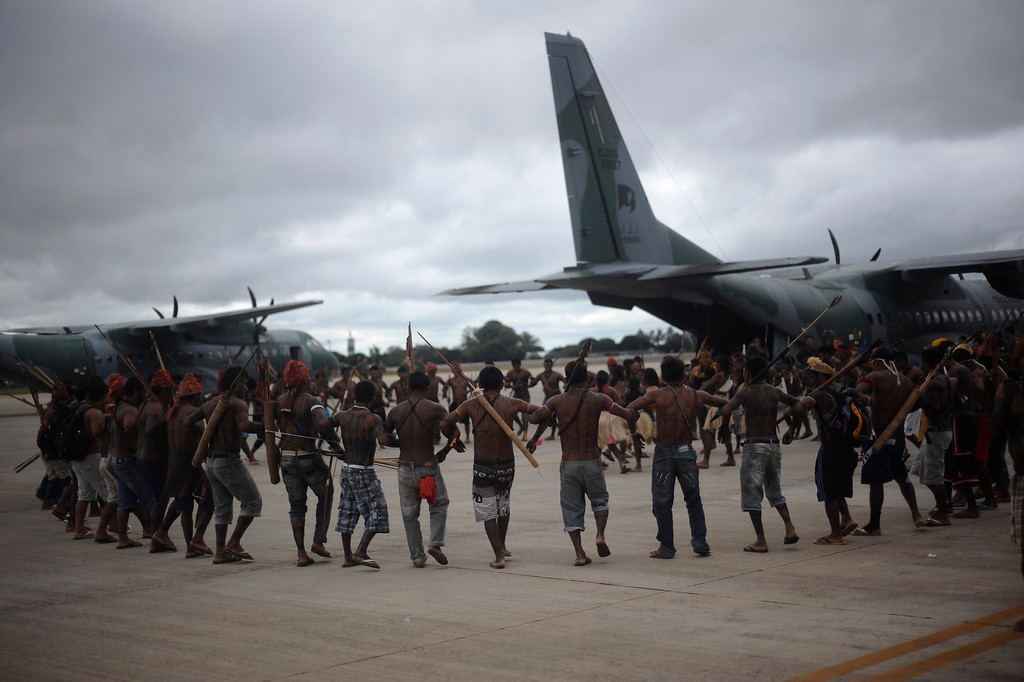 . Munduruku Indians do a dance around a Brazilian Air Force plane that transported them to Brasilia for talks with the government, in Brasilia June 4, 2013. Air Force planes flew 144 Munduruku Indians to Brasilia for talks to end a week-long occupation of the controversial Belo Monte dam on the Xingu River, a huge project aimed at feeding Brazil\'s fast-growing demand for electricity. REUTERS/Lunae Parracho