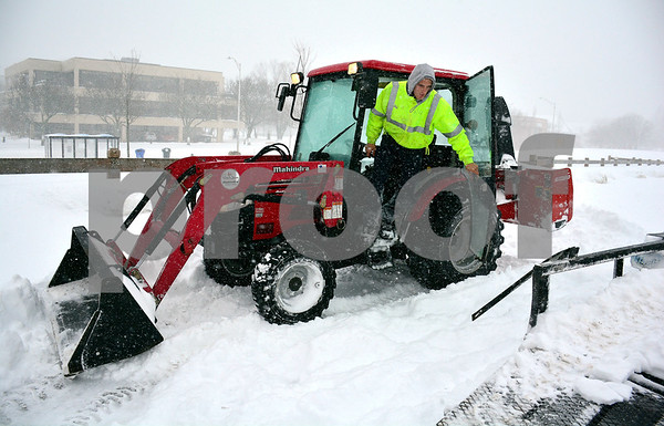 1/4/2018 Mike Orazzi | Staff Ryan Carrier prepares to clear snow in downtown Bristol during Thursday's snowfall.