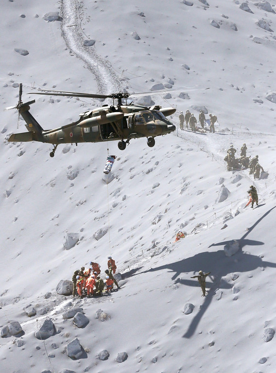 . A helicopter of the Japan Ground Self-Defense Force hovers over Mount Ontake to rescue climbers around the peak of the mountain in central Japan, Sunday, Sept. 28, 2014. Mount Ontake erupted shortly before noon Saturday, spewing large white plumes of gas and ash high into the sky and blanketing the surrounding area in ash. Rescue workers have found 30 or more people unconscious and believed to be dead near the peak of an erupting volcano in central Japan, local government and police said. (AP Photo/Kyodo News)