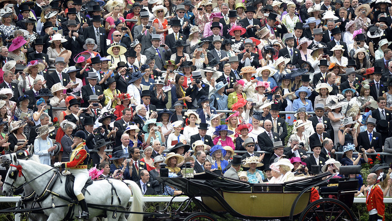 . Racegoers crowd around the parade ring as Britain\'s Queen Elizabeth II (2-R), Camilla, The Duchess of Cornwall (R) and Prince Charles, The Prince of Wales (R) arrive in a carriage during the first day of Royal Ascot, in Berkshire, west of London, on June 18, 2013. The five-day meeting is one of the highlights of the horse racing calendar. Horse racing has been held at the famous Berkshire course since 1711 and tradition is a hallmark of the meeting. Top hats and tails remain compulsory in parts of the course while a daily procession of horse-drawn carriages brings the Queen to the course.  ADRIAN DENNIS/AFP/Getty Images