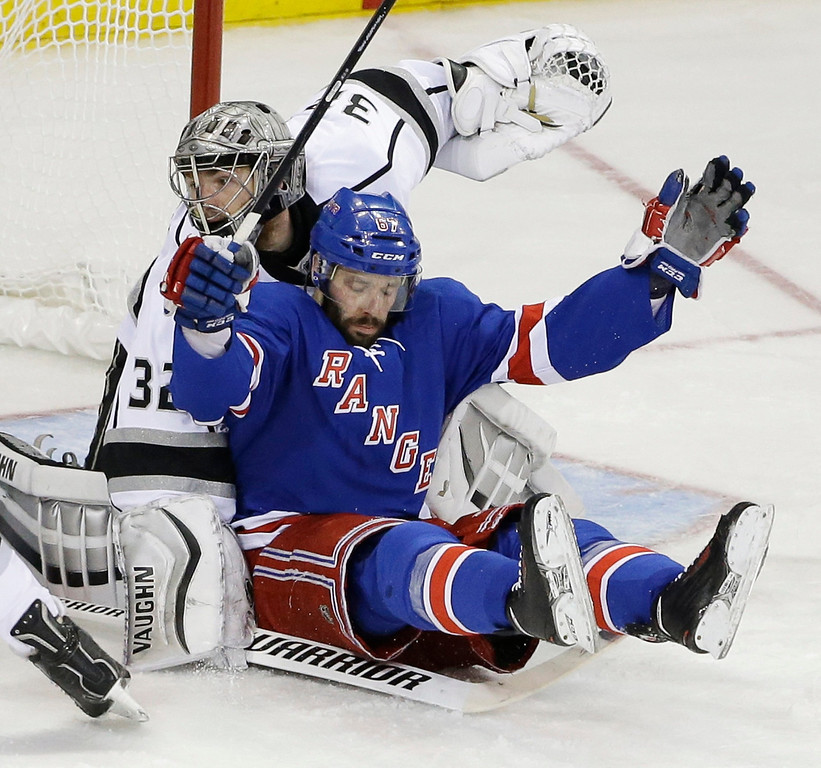 . New York Rangers right wing Martin St. Louis (26) falls back into Los Angeles Kings goalie Jonathan Quick (32) in the second during Game 3 of the NHL hockey Stanley Cup Final, Monday, June 9, 2014, in New York. (AP Photo/Frank Franklin II)