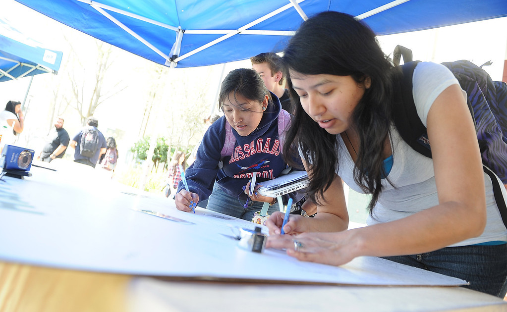 . Student Susanna Rodriguez signs a giant birthday card during a celebration of Rio Hondo Colleges 50th anniversary with a time capsule burial, cake and at Rio Hondo College on Thursday, March 14, 2013 in Whittier, Calif.  (Keith Birmingham Pasadena Star-News)