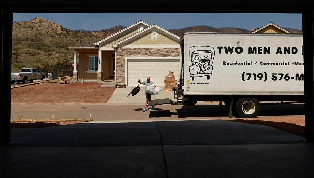 . Andy Perston unloads his belonging from a moving truck outside his newly built home in the Mountain Shadows neighborhood in Colorado Springs, June 20, 2013. Perston\'s home was destroyed in the Waldo Canyon fire. (Photo By RJ Sangosti/The Denver Post)