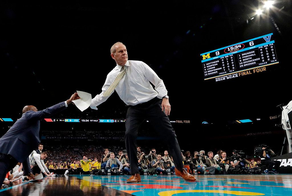 . Michigan head coach John Beilein hands the paper to the bench as he directs his team during the first half in the championship game of the Final Four NCAA college basketball tournament against Villanova, Monday, April 2, 2018, in San Antonio. (AP Photo/Eric Gay)